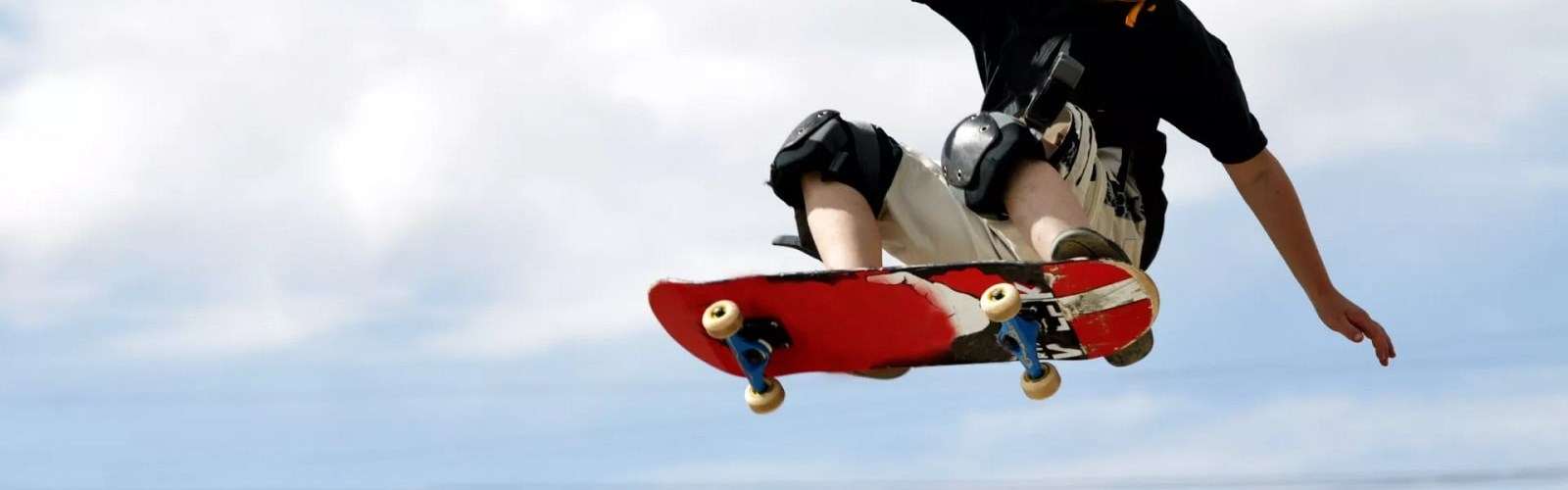Young boy riding skateboard with protective gear