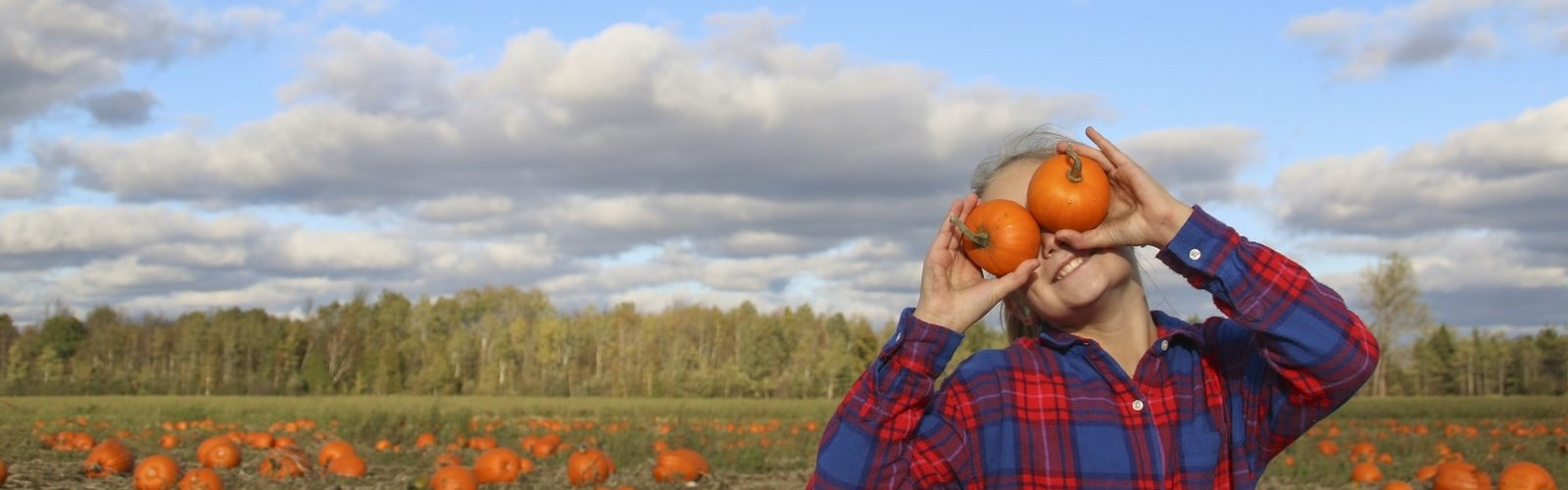 Girl in pumpkin fields holding up two pumpkins to her eyes